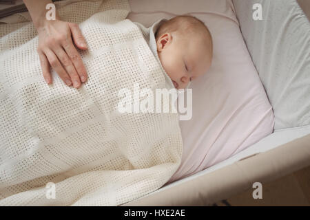 High angle view of mother hand on sleeping baby at home - Stock Photo