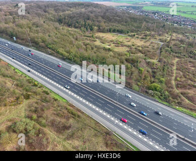Aerial view of cars on a motorway in an English countryside, between fields and woodland - Stock Photo