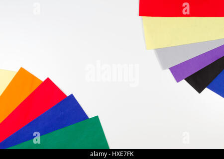 Selection of colorful felt sheets arranged as border frame on white background. Top view - Stock Photo