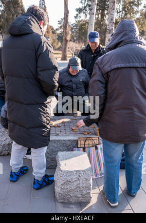 Elderly Chinese men playing Chinese checkers in the Temple of Heaven Park in Beijing, China. - Stock Photo