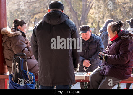 Elderly Chinese people enjoying their leisure time on a winter day at the Temple of Heaven Park in Beijing. - Stock Photo