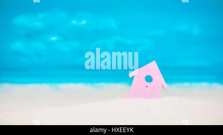 Symbol of little lilac house on the sand with bright cloudy blue painted sky background - Stock Photo