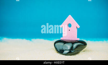 Symbol of little lilac house secured builed on black stone on blue background - Stock Photo