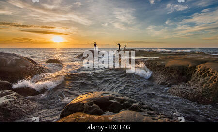 Silhouette of 3 fisherman fishing from rocks with waves and sunset background. The Tip of Borneo, Malaysia. - Stock Photo