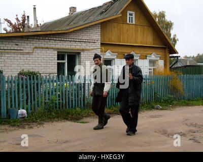 Two workmen walking home past a traditional wooden house in Vitebsk, Belarus. - Stock Photo