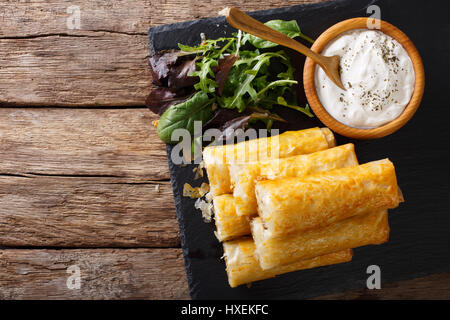 Moroccan food: briouat with meat, eggs and greens close-up on the table. Horizontal view from above - Stock Photo