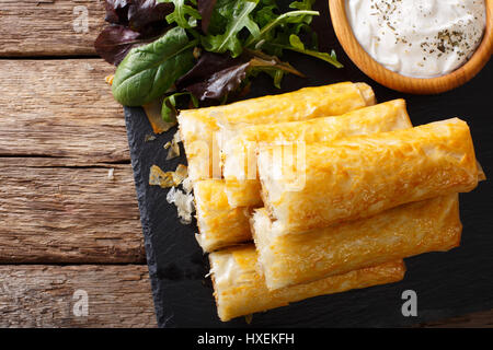 Filo rolls with meat, eggs and greens close-up and yogurt on the table. Horizontal view from above - Stock Photo
