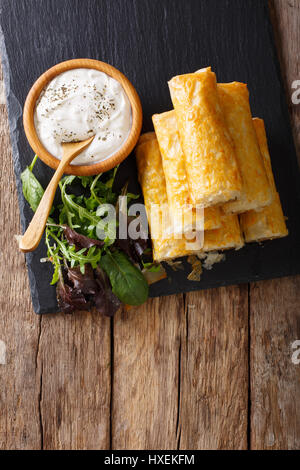 Filo rolls with meat, eggs and greens close-up and yogurt on the table. Vertical view from above - Stock Photo
