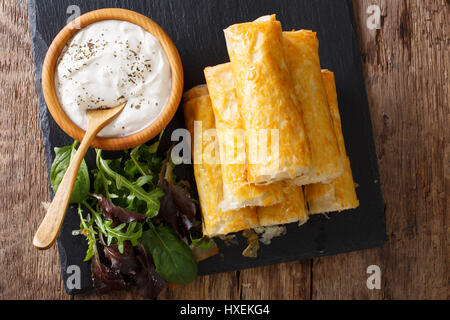 Rolls of filo stuffed with meat, eggs and greens close-up on the table. Horizontal view from above - Stock Photo