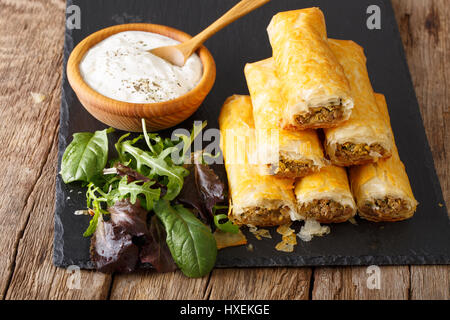 Crispy rolls borek stuffed with minced meat and eggs close-up on the table. horizontal - Stock Photo