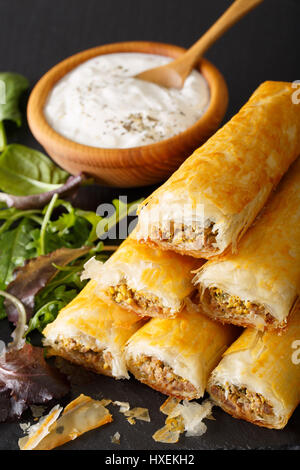 Filo rolls briouats with meat, eggs and greens close-up and yogurt on the table. vertical - Stock Photo