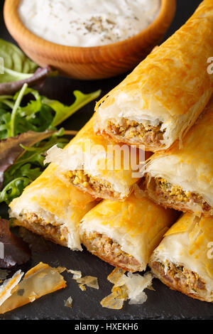 Filo rolls with meat, eggs and greens close-up and yogurt on the table. vertical - Stock Photo