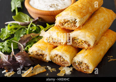 Delicious boregi with meat, eggs and greens close-up on the table. horizontal - Stock Photo