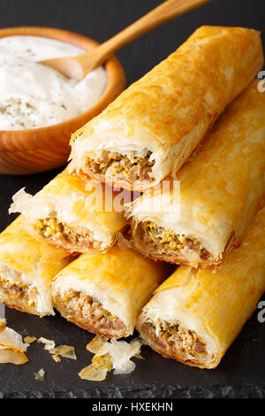 Rolls of filo stuffed with meat, eggs and greens close-up on the table. vertical - Stock Photo