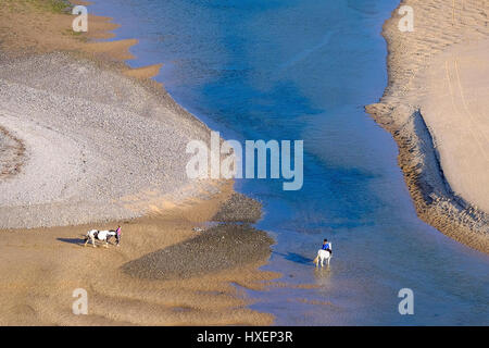 Horseriders on the beach at Three Cliffs Bay on the Gower Peninsula, South Wales, UK - Stock Photo