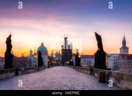 Prague, Czech Republic. Charles Bridge with its statuette and sunrise over the bridge, Old Town Bridge Tower in - Stock Photo