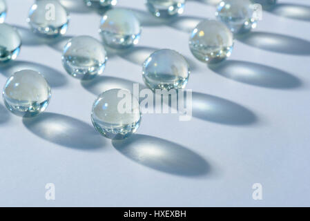 Clear glass marbles on a white surface bathed in a blue light - Stock Photo