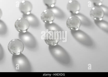 Clear glass marbles on a white surface bathed in light - Stock Photo