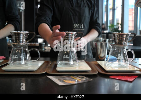A Barista Is Using A Kalita Wave Dripper To Brew Coffee At The Stock