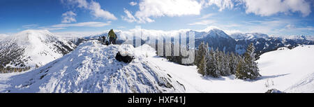 Fantastic alpine winter wonderland with panoramic view from the summit of a snowy mountain glowing by sunlight. - Stock Photo
