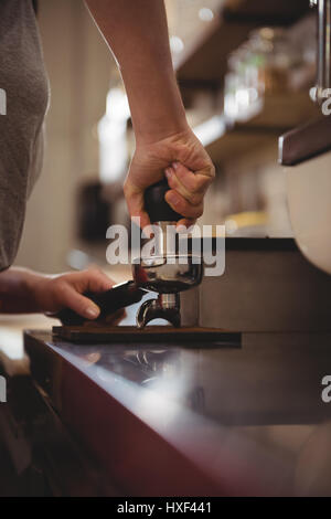 Cropped image of female barista tamping coffee in cafe - Stock Photo