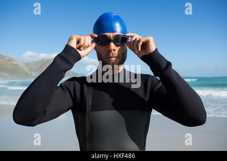 Athlete wearing swimming goggles by sea against sky - Stock Photo