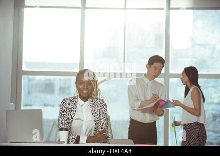 Portrait of female executive smiling while sitting at desk against colleagues discussing in background - Stock Photo