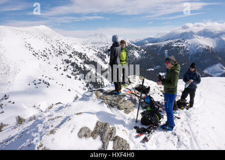Group of ski mountaineers having a break on top of a snowy mountain, Triebenfeldkogel, Styrian Alps, Austria. - Stock Photo