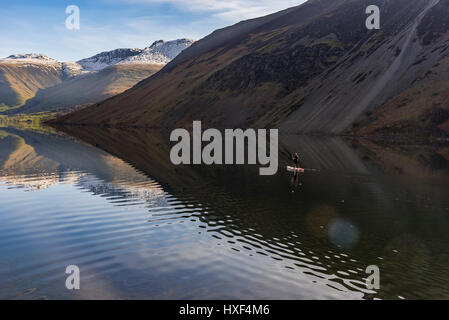Wastwater with flat calm still water and paddleboarder. - Stock Photo