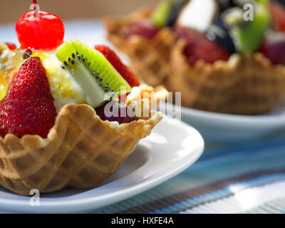 fruit ice cream sundae in waffle basket on table - Stock Photo