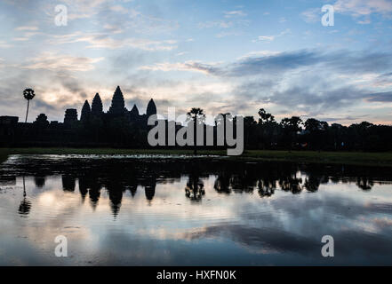 Stunning sunrise over Angkor Wat, as a silhouete, with the temple refleciting in water in Siem Reap, Cambodia. This - Stock Photo