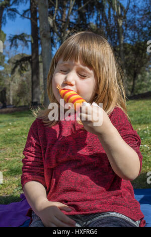 portrait of three years old blonde child, eating enjoying colorful orange and red ice lolly or popsicle, sitting - Stock Photo