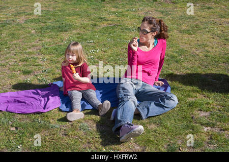 woman mother, with pink shirt and blue jeans, and three years old blonde child eating ice lolly, or popsicle, sitting - Stock Photo