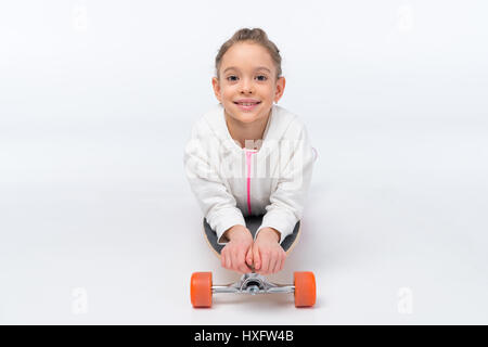 portrait of smiling girl lying on skateboard on white - Stock Photo