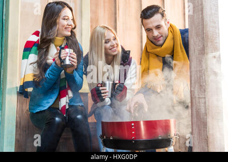 Happy young friends drinking hot tea and grilling meat on porch - Stock Photo