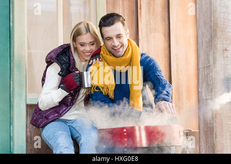 Happy young couple in warm clothes sitting together near grill on porch - Stock Photo