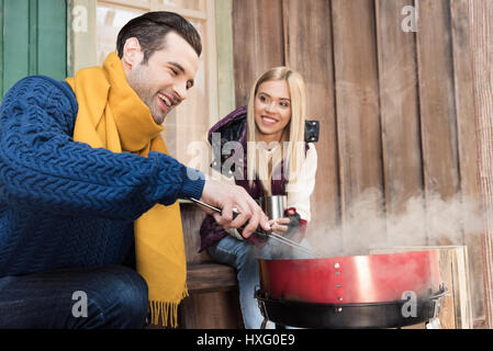 Smiling young woman with hot drink looking at happy man grilling meat on porch - Stock Photo