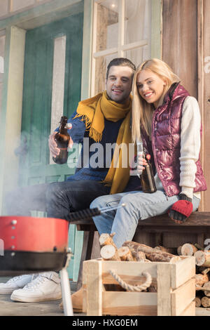 Happy young couple drinking beer and looking at grill on porch - Stock Photo