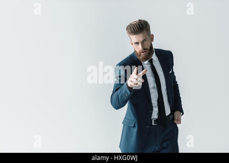 Handsome bearded businessman in stylish suit pointing at camera with finger - Stock Photo