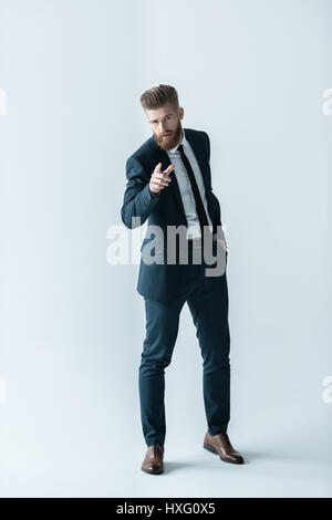 Stylish bearded businessman with hand in pocket pointing at camera with finger - Stock Photo