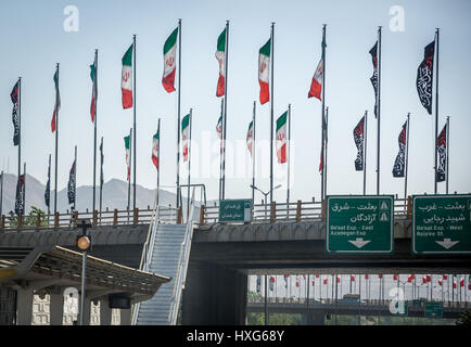 Iranian flags on a road above higway in Tehran city, capital of Iran and Tehran Province - Stock Photo