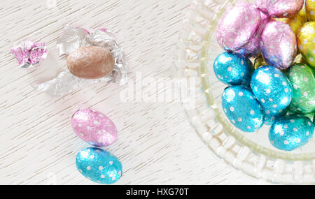 Chocolate eggs, foil wrappered, and  an unwrapped chocolate egg  beside a glass bowl full  of foil wrapped chocolate - Stock Photo