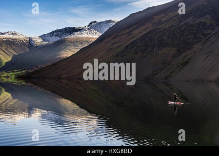 A lone paddlebaorder o0n the flatcalm waters of Wasdale - Stock Photo