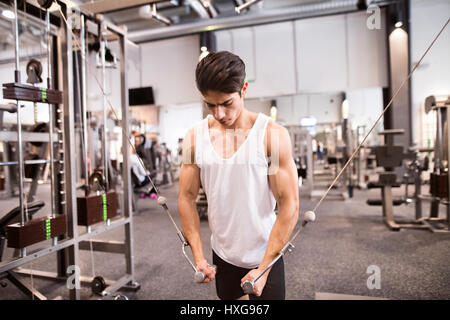 Young hispanic muscular body builder working out in gym on a cable machine, doing cable fly exercise for better - Stock Photo
