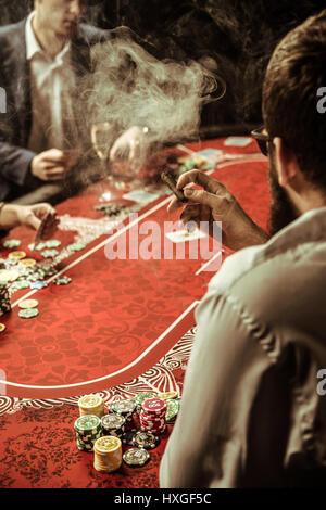 back view of smoking man playing poker in casino - Stock Photo