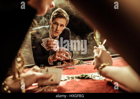 concentrated man with drink and poker cards looking at woman in casino - Stock Photo