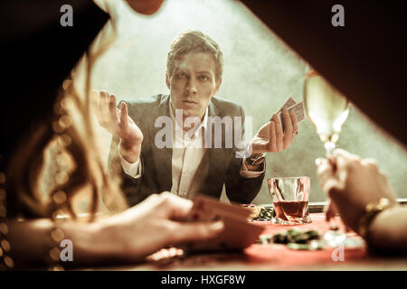 confused man with poker cards in hand looking at woman - Stock Photo