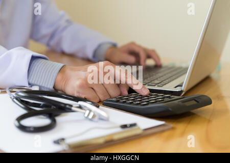 Doctor working in hospital use calculator, Healthcare and medical concept, stethoscope with clipboard, selective - Stock Photo