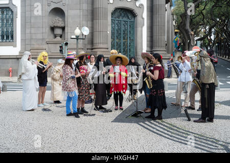 A musician in a multi coloured coat plays in a street band in Funchal - Stock Photo