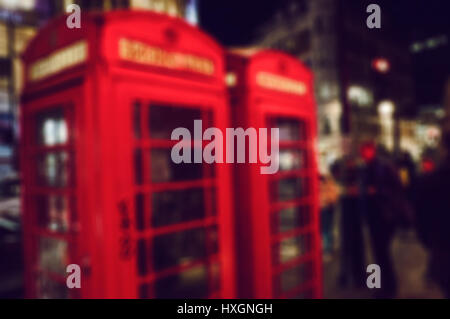 a defocused blur background of people walking in a street at night in London, United Kingdom, with two typical red - Stock Photo